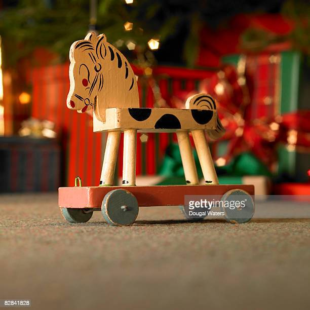 Toy horse with christmas presents in background.