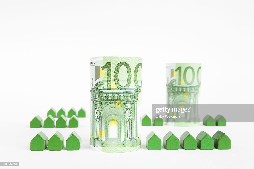 Green model houses with Euro currency, close-up