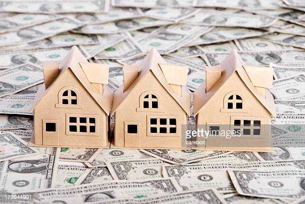 3 toy houses on a pile of $1 00 bills
