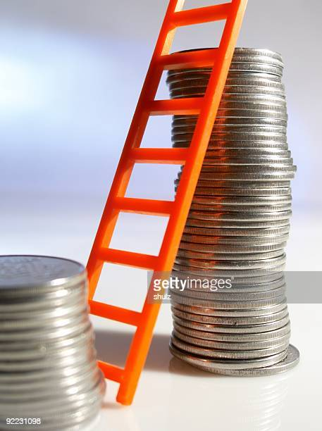 Toy ladder leaning on a pile of coins
