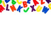 Top border of colorful toy magnetic alphabet letters over a white background