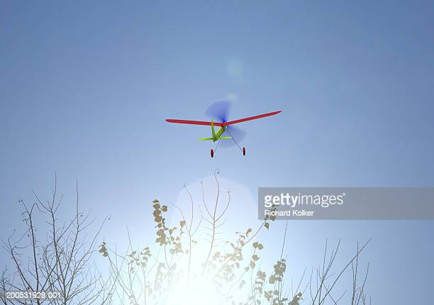 Toy plane flying above treetops