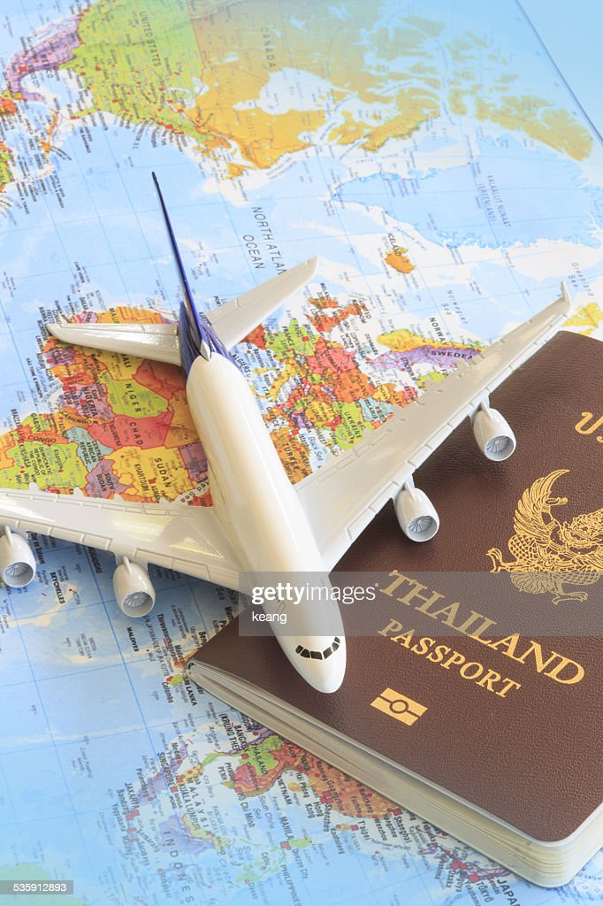 Toy plane resting on a thailand passport and world map : Stock Photo