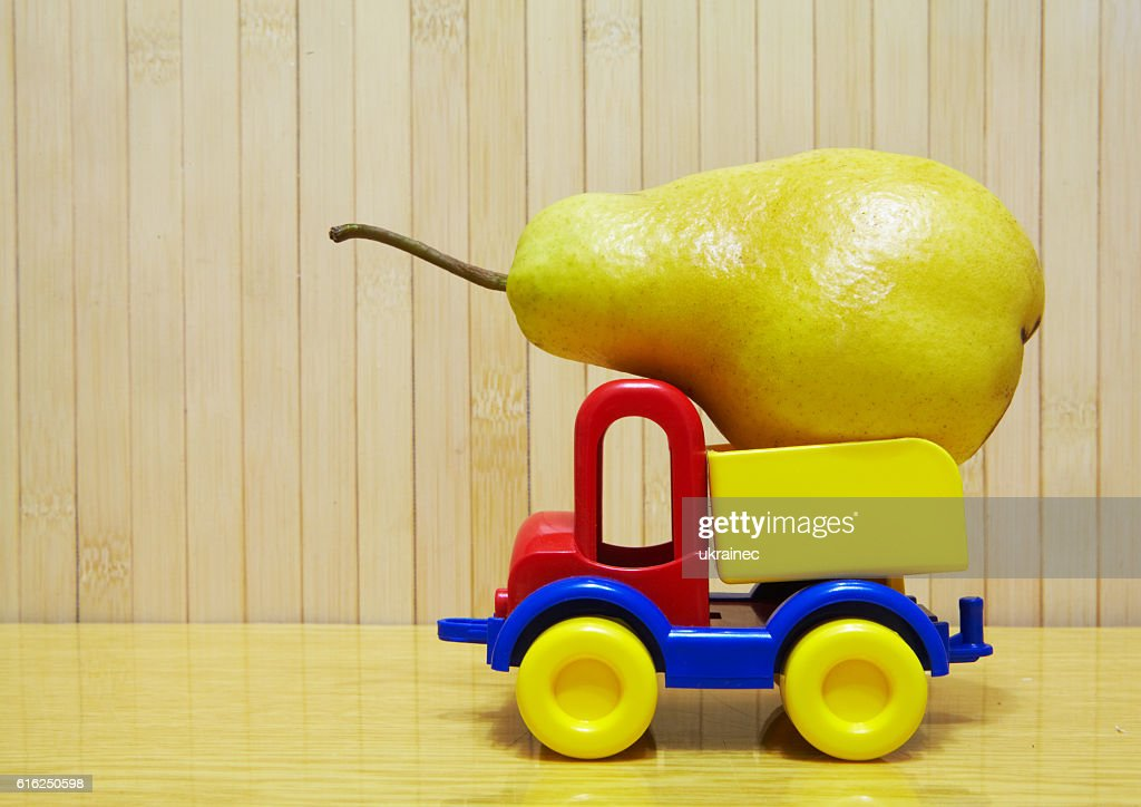Toy plastic car with pear : Foto de stock