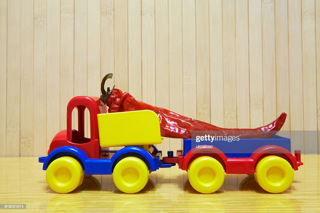 Toy plastic car with red pepper : Stock Photo