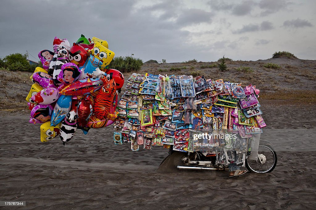 A toy seller rides on 'sea of sands' as Indonesian muslims people perform Eid Al-Fitr prayer at Parangkusumo beach on August 8, 2013 in Yogyakarta, Indonesia. Eid Al-Fitr, marks the end of Ramadan, the Islamic month of fasting and begins after the sighting of a new crescent moon.