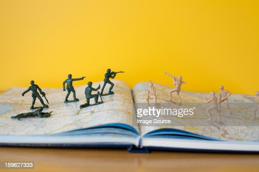 Toy soldiers fighting on map : Stock Photo
