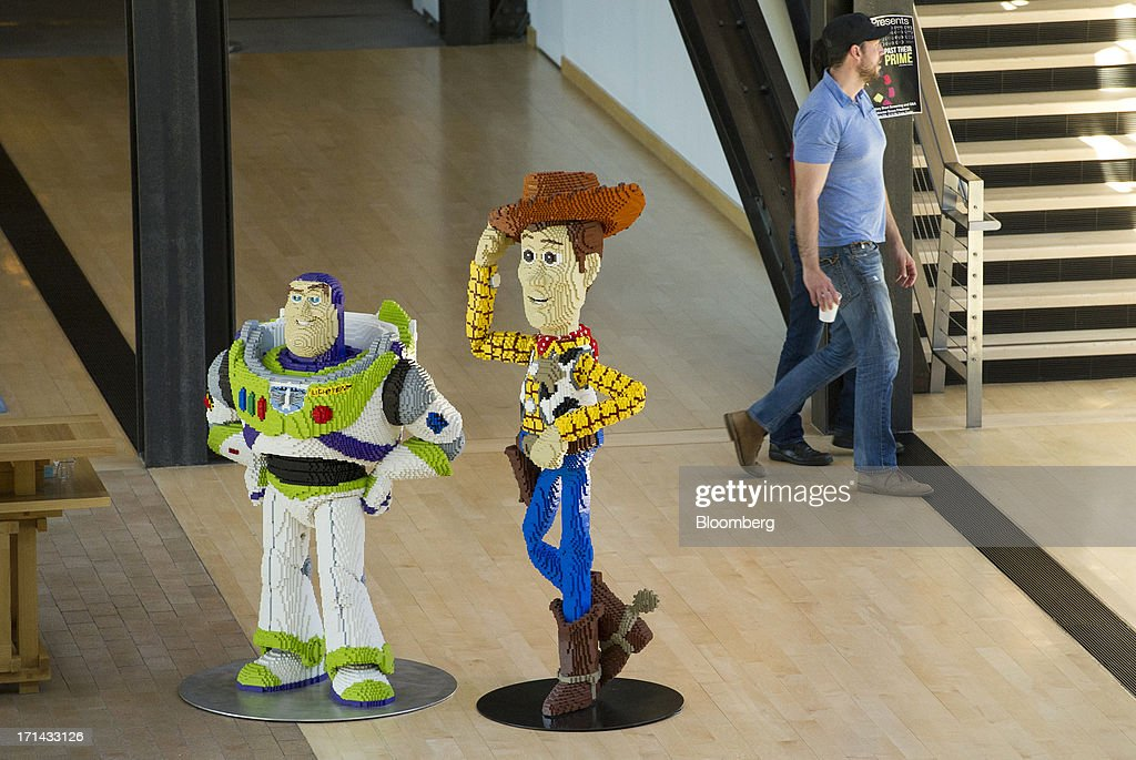 'Toy Story' character cut-outs stand as people walk in the halls at the Pixar Animation Studios headquarters in Emeryville, California, U.S., on Friday, June 21, 2013. Walt Disney Co.s Pixar animation 'Monsters University' took first place at U.S. and Canadian theaters this past weekend with $82 million in ticket sales, overcoming Brad Pitts zombie apocalypse tale 'World War Z,' which was second with $66 million. Photographer: David Paul Morris/Bloomberg via Getty Images