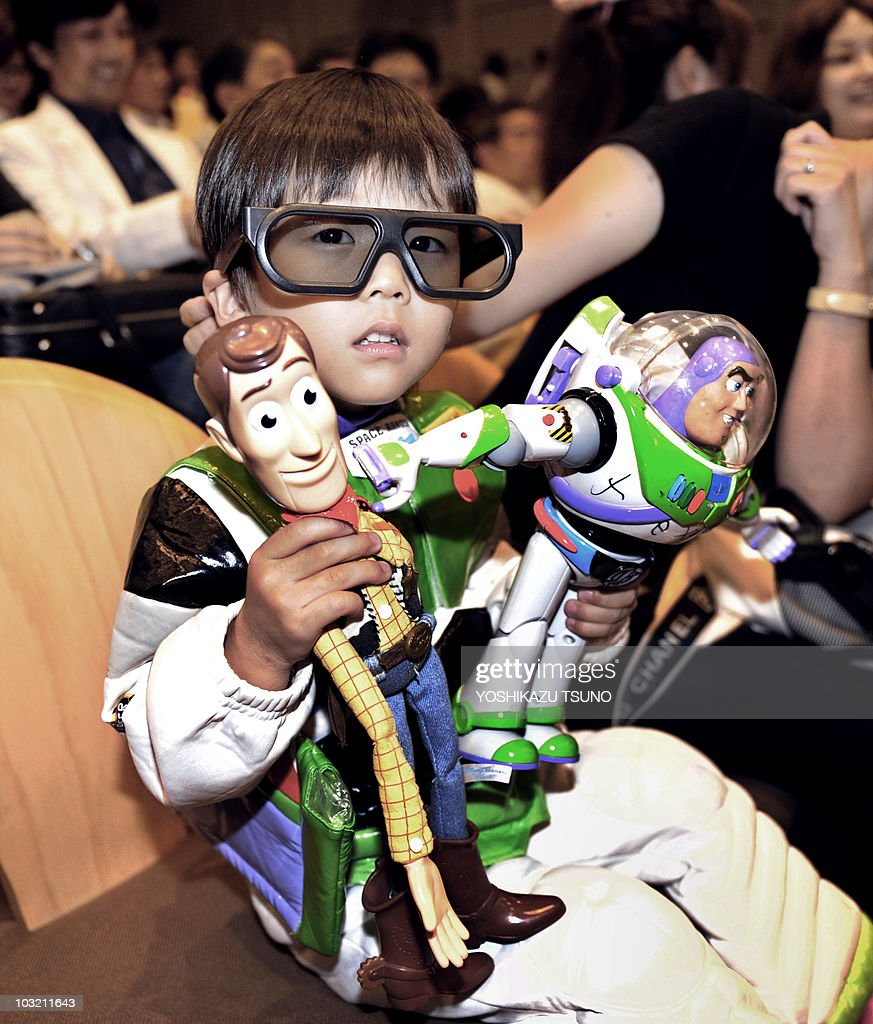 Toy story fan wears a special 3d glasses and holds his favorirte toys