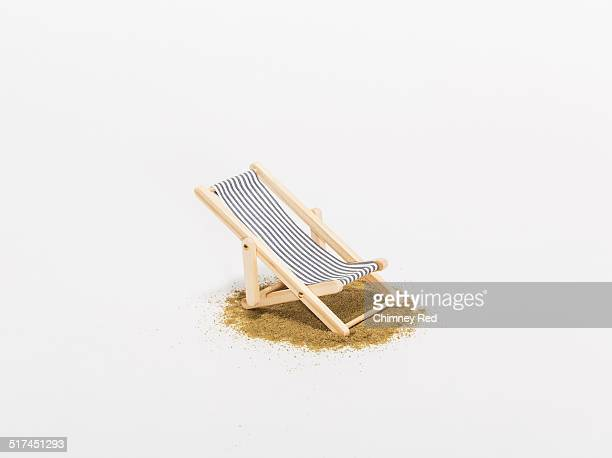 Toy sunbathing chair on sand