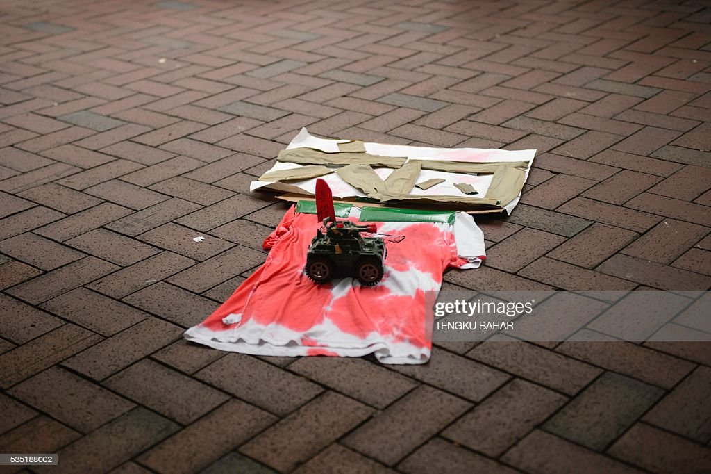 A toy tank rolls over a t-shirt, stained in red to mimic blood and with characters that read '64' to commemorate the June 4, 1989 Tiananmen Square crackdown against pro-democracy activists, during a rally in Hong Kong on May 29, 2016. People will gather in Hong Kong on June 4 for the annual remembrance ceremony to mark the 27th anniversary of the Tiananmen Square crackdown. / AFP / TENGKU