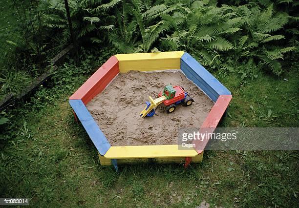 A toy truck in a sandbox