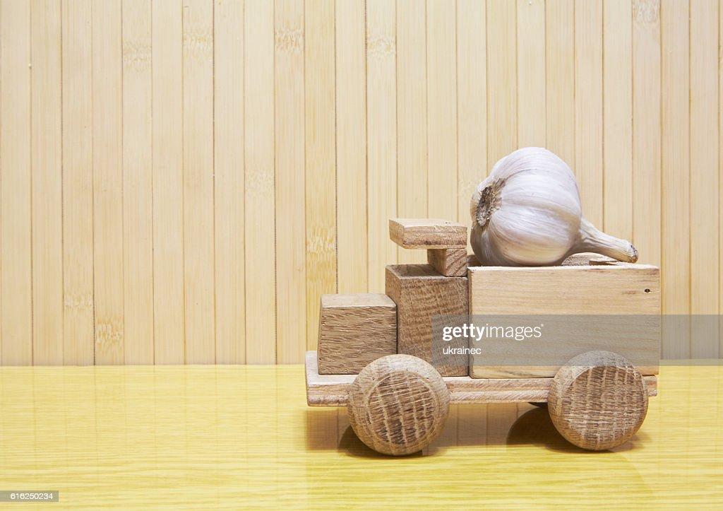 Toy wooden car with garlic : Foto de stock