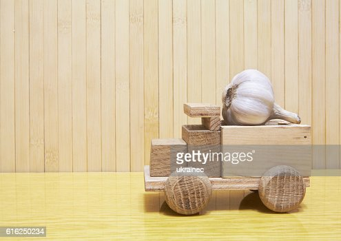 Toy wooden car with garlic : Stock Photo