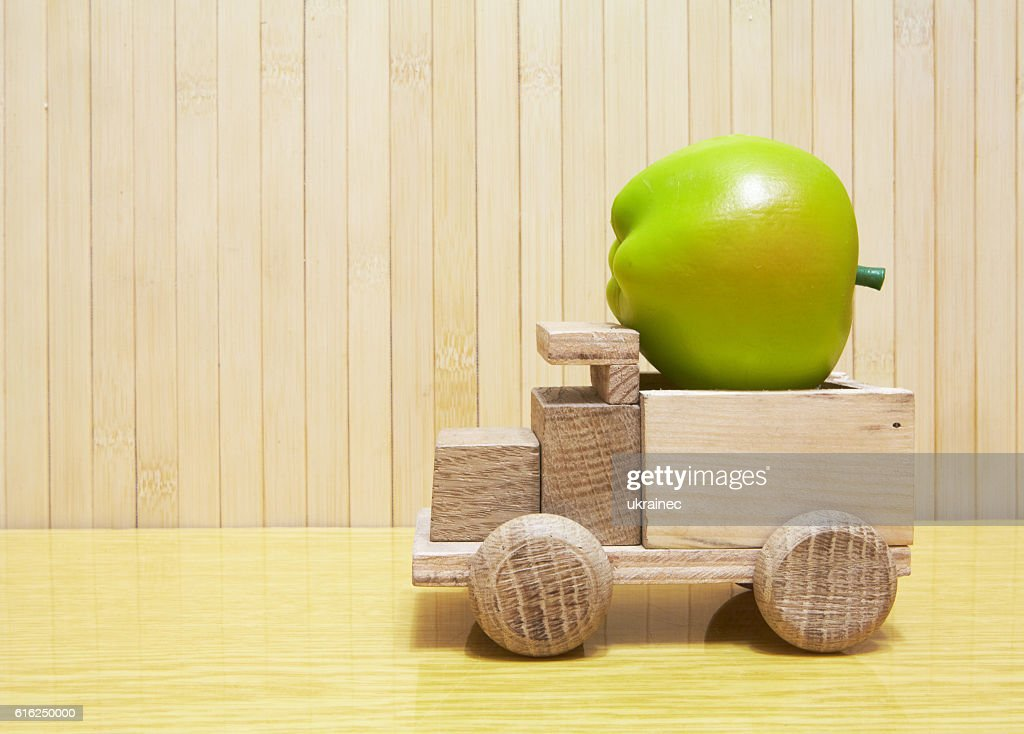 Toy wooden car with green apple : Foto de stock