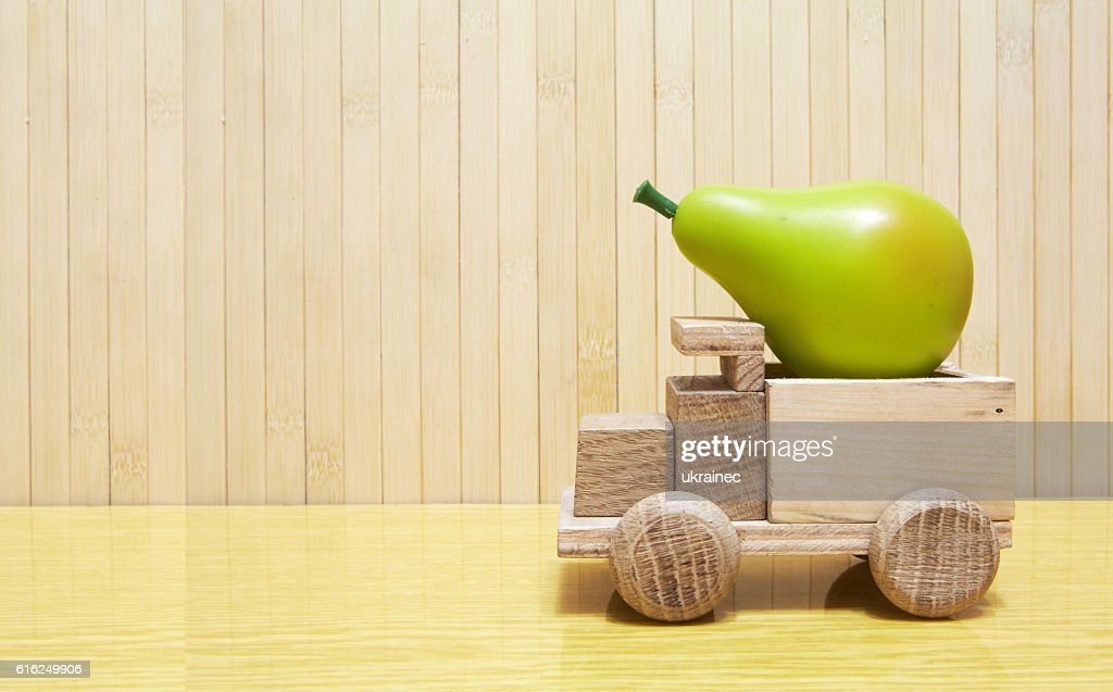 Toy wooden car with green pear : Foto de stock