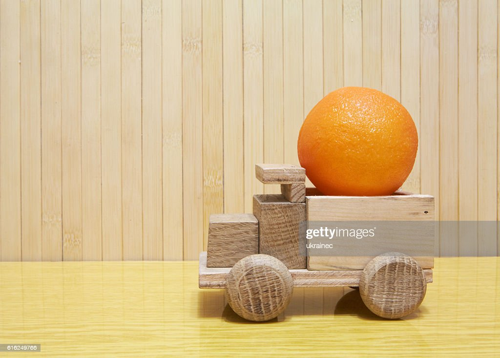 Toy wooden car with orange : Foto de stock