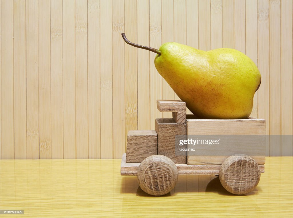 Toy wooden car with yellow pear : Foto de stock