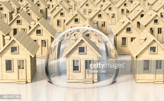 Toy wooden miniature houses, one under glass dome : Stock Photo