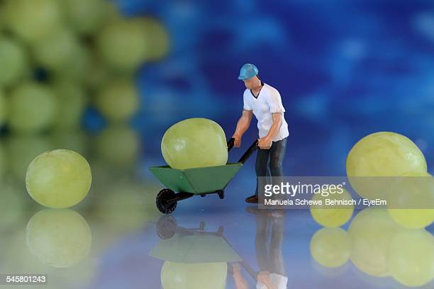 Toy Worker Pushing Grape In Wheelbarrow