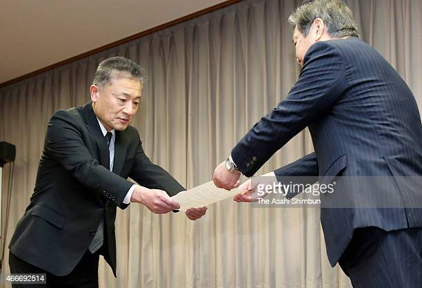 Toyo Tire Rubber president Takuji Yamamoto is handed the instruction document by deputy land minister Issei Kitagawa during his visit to the Ministry...