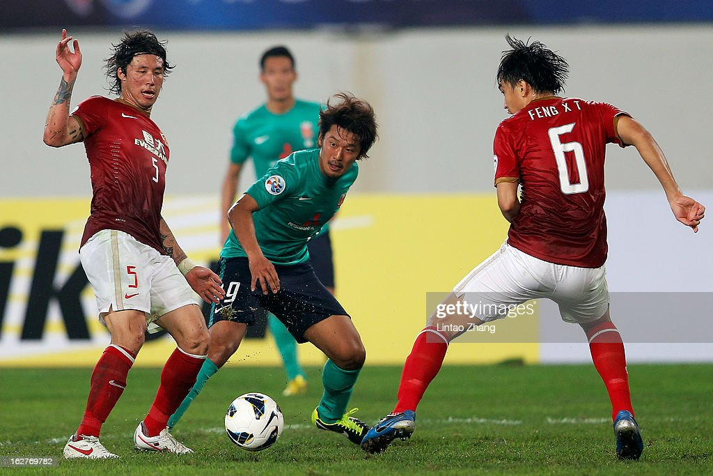 Toyofumi Sakano (C) of Urawa Red Diamonds challenges Zheng Linpeng (L) and Feng Xiaoting of Guangzhou Evergrande during the AFC Champions League Group F match between Guangzhou Evergrande and Urawa Red Diamonds at Tianhe Stadium on February 26, 2013 in Guangzhou, China.