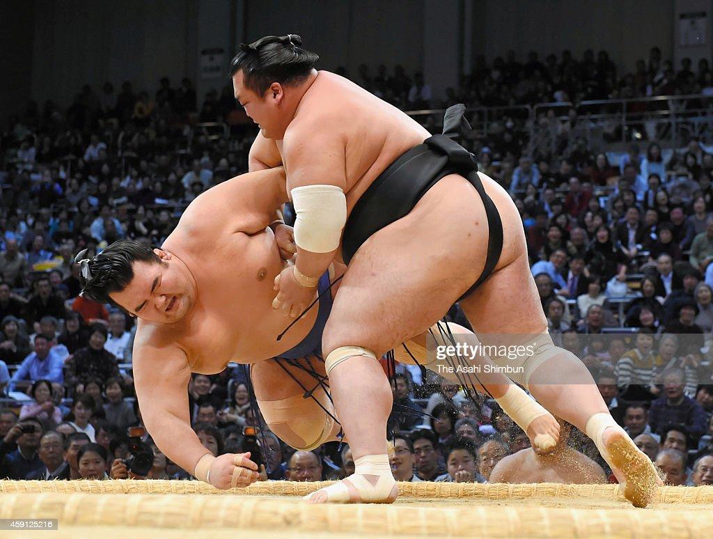 Toyohibiki throws ozeki Kotoshogiku to win during day seven of the Grand Sumo Kyushu Tournament at Fukuoka Covention Center on November 15 2014 in...