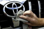 Toyota car dealer employee cleaning the logo on a front of a Toyota RAV4