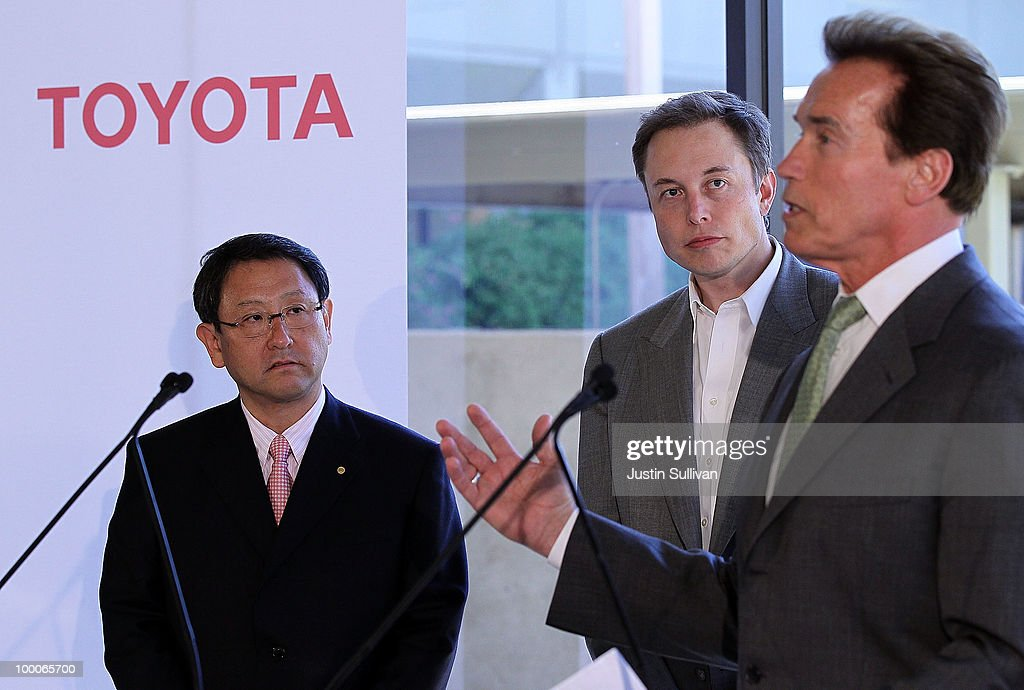 Toyota CEO Akio Toyoda and Tesla Motors CEO Elon Musk look on as California governor Arnold Schwarzenegger speaks during a news conference at Tesla Motors headquarters May 20, 2010 in Palo Alto, California. Electric car maker Tesla Motors annoucned a partnership with Japanese automaker Toyota to make electric cars in the United States. The cars will be manufactured at the recently shuttered NUMMI plant in Fremont, California where Toyota had pulled out after a joint partnership with General Motors had ended.