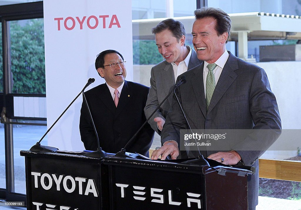 Toyota CEO Akio Toyoda, Tesla Motors CEO Elon Musk and California governor Arnold Schwarzenegger laugh during a news conference at Tesla Motors headquarters May 20, 2010 in Palo Alto, California. Electric car maker Tesla Motors annoucned a partnership with Japanese automaker Toyota to make electric cars in the United States. The cars will be manufactured at the recently shuttered NUMMI plant in Fremont, California where Toyota had pulled out after a joint partnership with General Motors had ended.