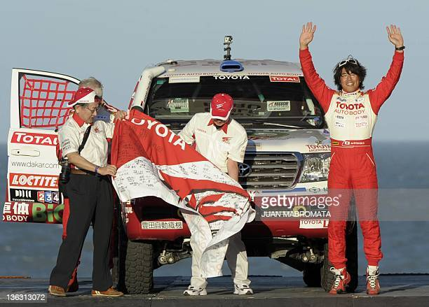 Toyota driver Jun Mitsuhashi of Japan and codriver Alain Guehennec of France pose on the podium during the symbolic start of the 2012 Dakar Rally in...