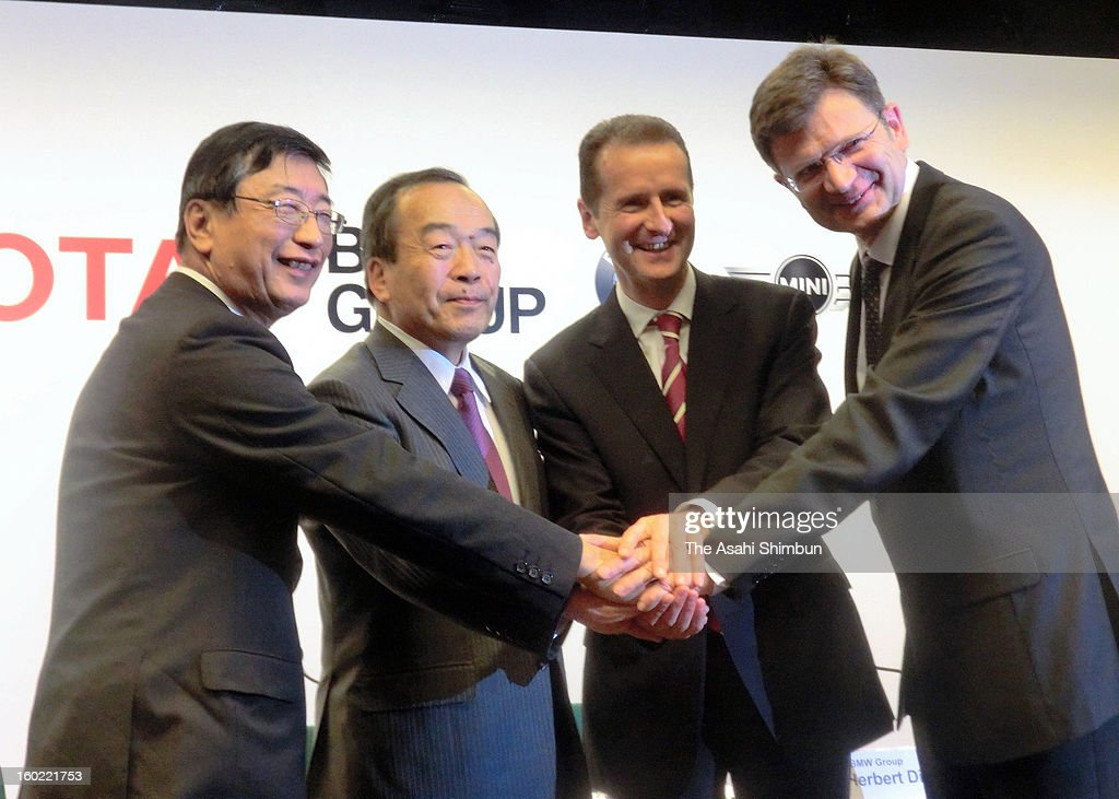 Toyota Motor Co director and senior managing officer Yasumori Ihara, vice chairman Takeshi Uchiyamada, BMW development chief Herbert Diess and senior vice president Klaus Froehlich shake hands during a press conference on January 24, 2013 in Nagoya, Aichi, Japan. Toyota Motor Corp. and BMW Group will start joint research on 'lithium-air batteries,' which are expected to outperform the lithium-ion batteries currently used in plug-in gas-electric hybrid and other vehicles.