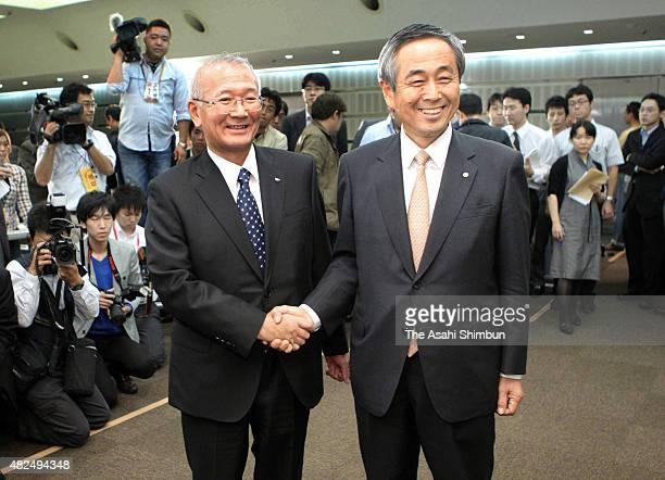 Toyota Motor Co Executive Vice President Yoichiro Ichimaru and Daihatsu Motor Co President Koichi Ina shake hands during a press conference on...
