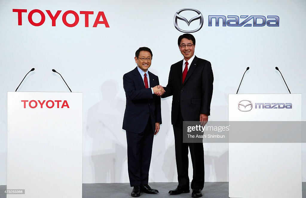 Toyota Motor Co President <a gi-track='captionPersonalityLinkClicked' href=/galleries/search?phrase=Akio+Toyoda&family=editorial&specificpeople=2334399 ng-click='$event.stopPropagation()'>Akio Toyoda</a> (L) and Mazda Motor Co President <a gi-track='captionPersonalityLinkClicked' href=/galleries/search?phrase=Masamichi+Kogai&family=editorial&specificpeople=10904432 ng-click='$event.stopPropagation()'>Masamichi Kogai</a> (R) shake hands during a press conference on May 13, 2015 in Tokyo, Japan. Two Japanese automakers agreed to expand their partnership to eco-friendly and advanced safety technology.