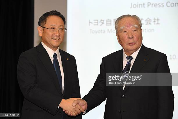 Toyota Motor Co President Akio Toyoda and Suzuki Motor Co Chairman Osamu Suzuki shake hands during a joint press conference at the Toyota's Tokyo...