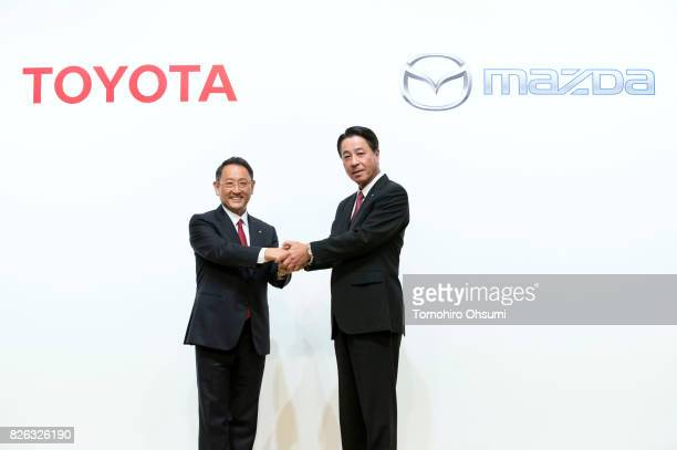 Toyota Motor Co President Akio Toyoda left and Mazda Motor Co President and CEO Masamichi Kogai right shake hands during a photo session at a joint...