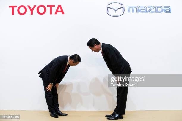Toyota Motor Co President Akio Toyoda left and Mazda Motor Co President and CEO Masamichi Kogai right bow during a photo session at a joint press...