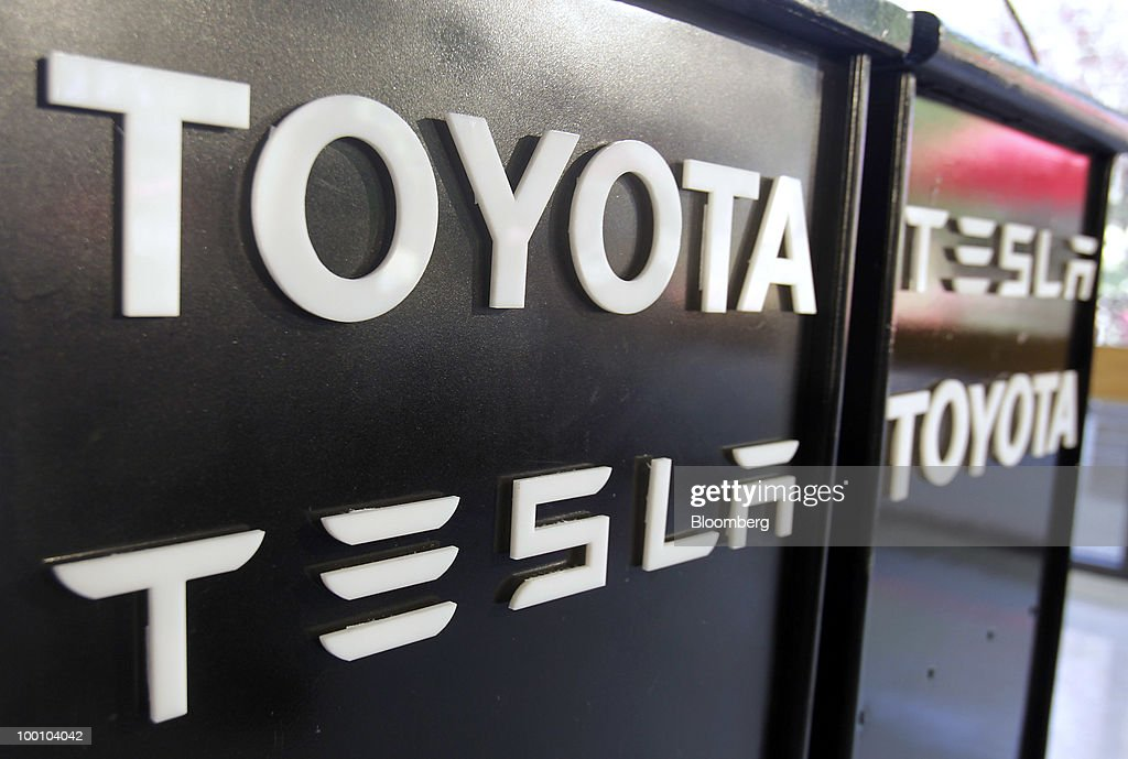 Toyota Motor Corp. and Tesla Motors Inc. logos appear on a podium before a news conference at the Tesla Motors Inc. headquarters in Palo Alto, California, U.S., on Thursday, May 20, 2010. Toyota Motor Corp. will acquire a $50 million stake in California electric-car maker Tesla Motors Inc. as automakers compete to introduce less-polluting vehicles in the U.S. Photographer: Tony Avelar/Bloomberg via Getty Images