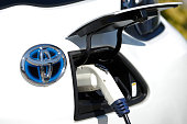 A Toyota Motor Corp badge is displayed on an eQ compact electric vehicle sits charging while parked outside outside a model smart home in Toyota's...