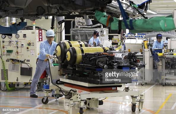 A Toyota Motor Corp employee pushes a cart carrying the hydrogen tanks of a Mirai fuelcell vehicle on the production line of the company's Motomachi...