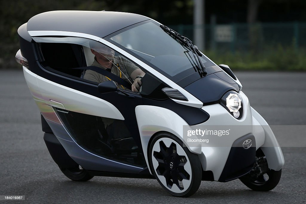 A Toyota Motor Corp. i-ROAD electric personal mobility vehicle (PMV) is test driven during a media briefing on the company's advanced technologies in Tokyo, Japan, on Thursday, Oct. 10, 2013. Toyota, the worlds largest automaker, will introduce systems in about two years enabling cars to communicate with each other to avoid collision. Photographer: Kiyoshi Ota/Bloomberg via Getty Images
