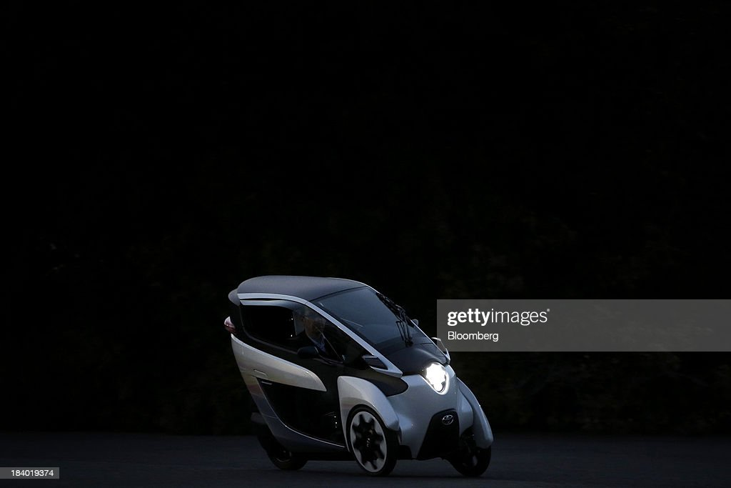A Toyota Motor Corp. i-ROAD electric personal mobility vehicle (PMV) is test driven at dusk during a media briefing on the company's advanced technologies in Tokyo, Japan, on Thursday, Oct. 10, 2013. Toyota, the worlds largest automaker, will introduce systems in about two years enabling cars to communicate with each other to avoid collision. Photographer: Kiyoshi Ota/Bloomberg via Getty Images