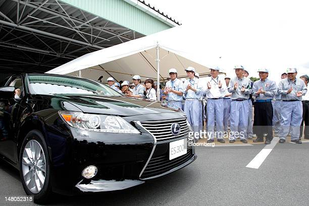 A Toyota Motor Corp Lexus ES300h sedan is driven as employees applaud during a lineoff ceremony for the company's Lexus ES series sedans at Toyota...