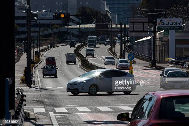 A Toyota Motor Corp Prius hybrid vehicle drives along a road in Toyota City Aichi Prefecture Japan on Friday Jan 18 2013 Toyota Motor Corp poised to...