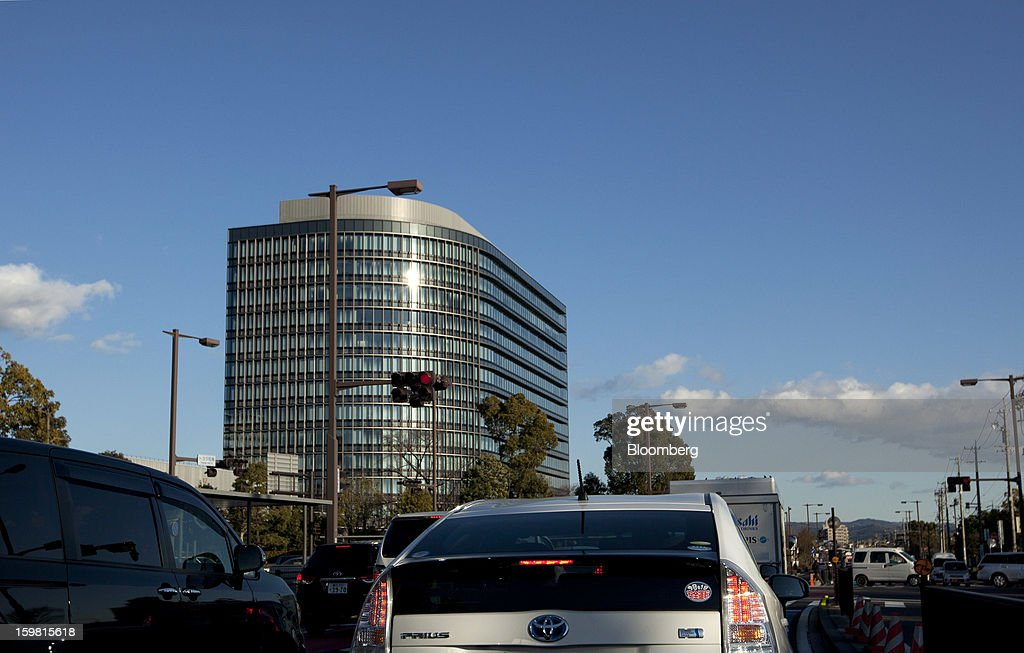 A Toyota Motor Corp. Prius hybrid vehicle drives past the company's headquarters in Toyota City, Aichi Prefecture, Japan, on Friday, Jan. 18, 2013. Toyota Motor Corp., poised to regain its title as the world's biggest carmaker this year, said last month its vehicle sales may rise 2 percent next year to a record, led by demand from overseas markets. Photographer: Tomohiro Ohsumi/Bloomberg via Getty Images