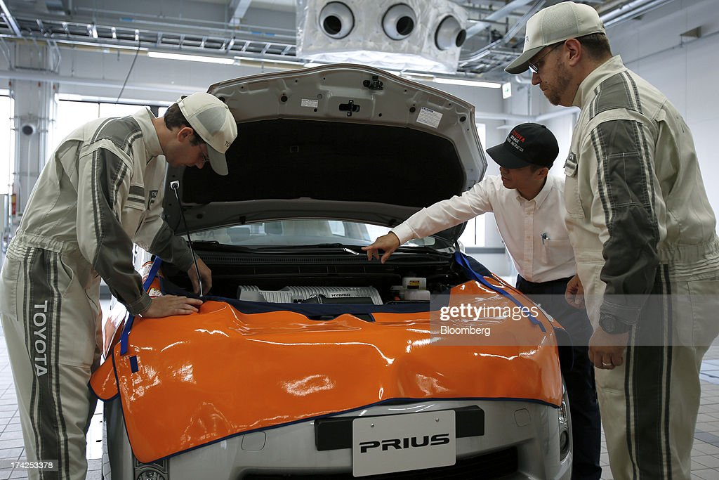 A Toyota Motor Corp. service technical instructor, second right, conducts maintenance training with trainee after-service staff as they work on a Prius hybrid vehicle during a demonstration at the company's Tajimi service center in Tajimi, Gifu Prefecture, Japan, on Monday, July 22, 2013. Toyota is the world's largest car maker. Photographer: Kiyoshi Ota/Bloomberg via Getty Images