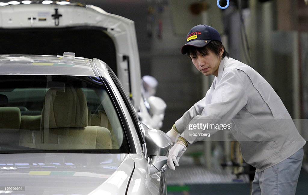 A Toyota Motor Corp. worker makes a final inspection of the company's Crown sedan at its Motomachi plant in Toyota City, Aichi Prefecture, Japan, on Thursday, Jan. 17, 2013. Toyota probably has regained its spot as the world's top-selling automaker after losing it in 2011 following disasters in Asia that hurt its ability to make cars and trucks. Photographer: Tomohiro Ohsumi/Bloomberg via Getty Images