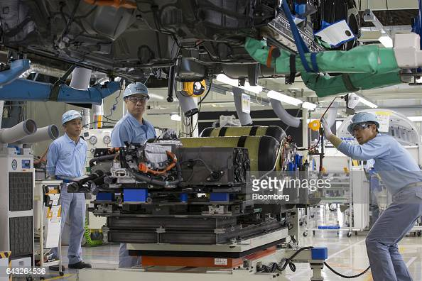 Toyota Motor Corp workers install hydrogen tanks in a Mirai fuelcell vehicle on the production line of the company's Motomachi plant in Toyota City...