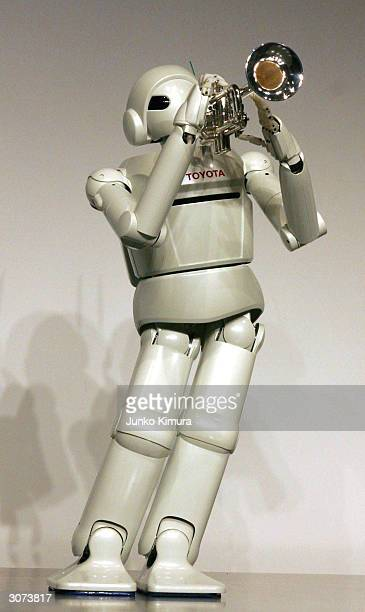 Toyota Motor Corporation's newly developed prototype of a walking robot blows and plays a trumpet during a press conference on March 11 2004 in Tokyo...
