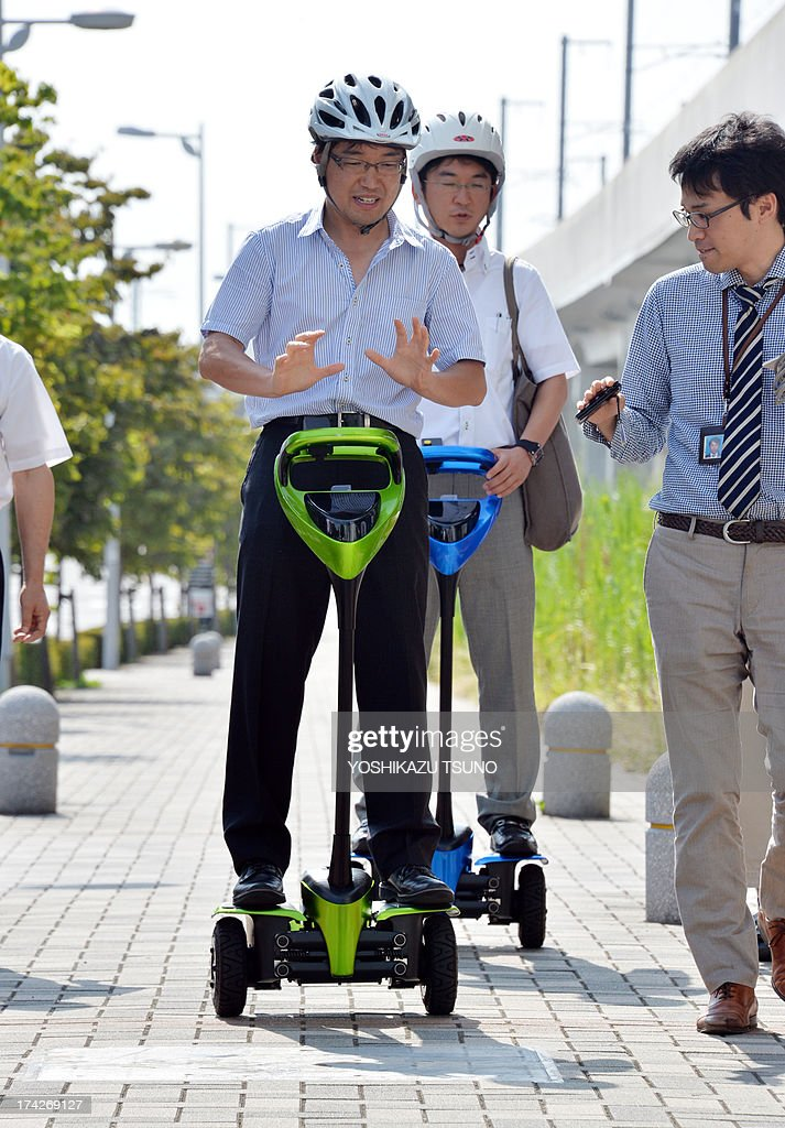 Toyota Motor engineers ride on Toyota's transport assistance robot, called the 'Winglet', during a demonstration on a public sidewalk in Tsukuba City, suburban Tokyo on July 23, 2013. Toyota and Tsukuba City started to field test the next generation of 'personal mobility robot' on the public thoroughfare, with trial runs scheduled until 2016. AFP PHOTO / Yoshikazu TSUNO